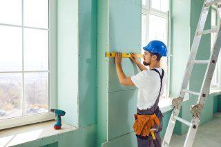 drywall installer measuring a wall